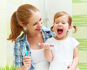 a smiling mother with a child before her first visit at Sussex Dental